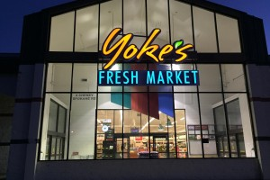 Yoke's Cheney front of building lit up at night with Yoke's Fresh Market logo