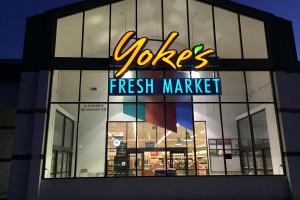 Yoke's Cheney front of building lit up at night with Yoke's Fresh Market logo